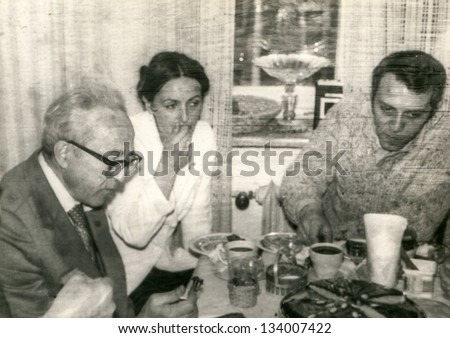 Vintage photo of a young couple with their father/father in law during a family party, seventies - stock photo