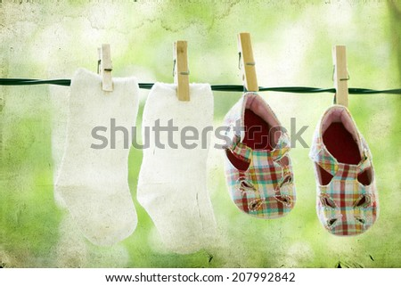 Vintage photo of baby clothes hanging on the clothesline. - stock photo