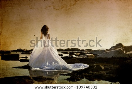 Vintage photo of beautiful bride standing on a cliff on the sea - stock photo