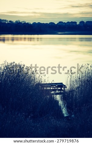 Vintage photo of beautiful sunset over calm lake.  - stock photo