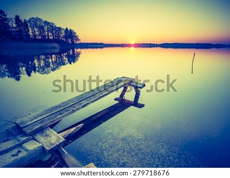 Vintage photo of beautiful sunset over calm lake. Landscape photographed in Mazury lake district. - stock photo