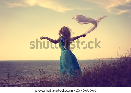 Vintage Photo of Blonde Woman with Scarf at the Sea. Toned Photo with Copy Space. Solitude Concept. - stock photo