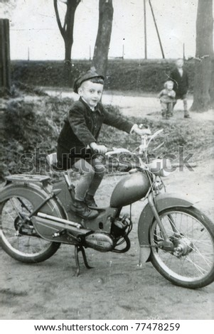 Vintage photo of boy on motorbike (early sixties) - stock photo