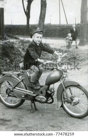 Vintage photo of boy on motorbike (early sixties) - stock photo