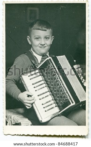 Vintage photo of boy playing an accordion (fifties) - stock photo