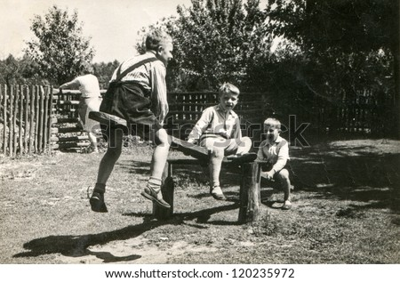 Vintage photo of boys playing on wooden swing (fifties) - stock photo