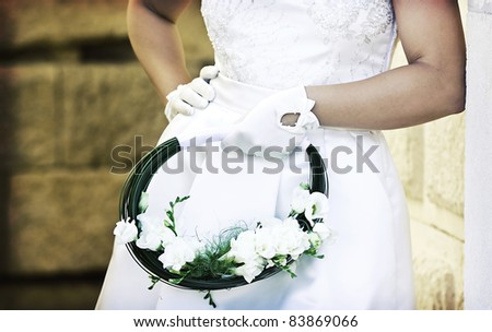 Vintage photo of bride's hands holding wedding bouquet