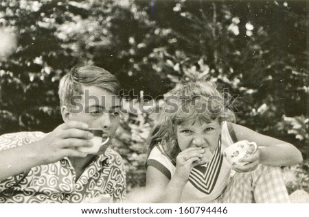 Vintage photo of brother and little sister eating outdoor - fifties - stock photo