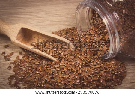 Vintage photo of brown linseed, flax seeds spilling out of glass jar on wooden background, concept for healthy nutrition - stock photo