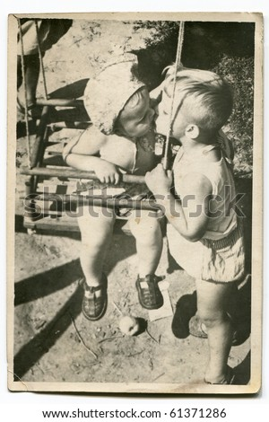 Vintage photo of children kissing - stock photo