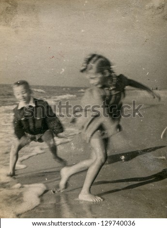 Vintage photo of children running on beach (visible motion blur) - fifties