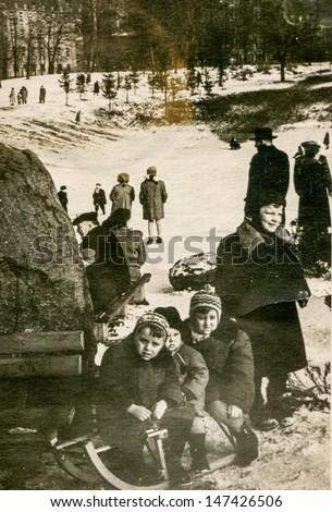 Vintage photo of children sledding, fifties - stock photo