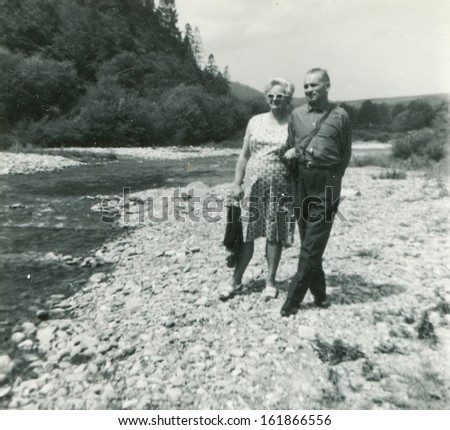 Vintage photo of couple on riverside, fifties - stock photo