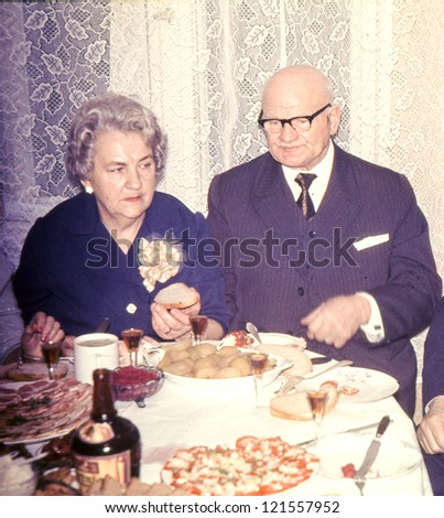 Vintage photo of elderly couple celebrating their anniversary (seventies) - stock photo