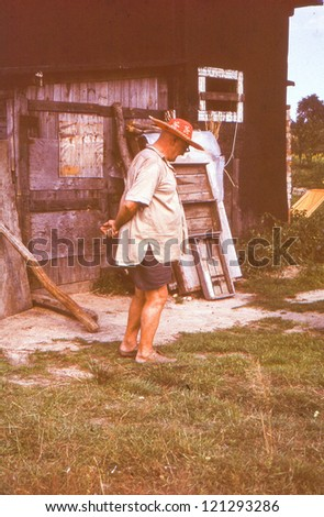 Vintage photo of elderly farmer in straw hat (sixties) - stock photo