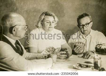 Vintage photo of elderly father playing cards with his adult daughter an son in law, sixties - stock photo
