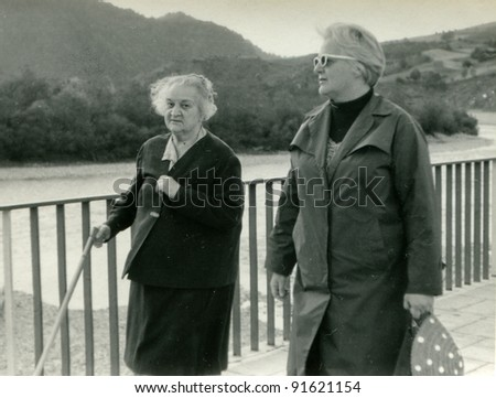 Vintage photo of elderly mother and adult daughter walking (sixties) - stock photo