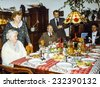Vintage photo of elderly woman and her family during a Christmas dinner, eighties - stock photo