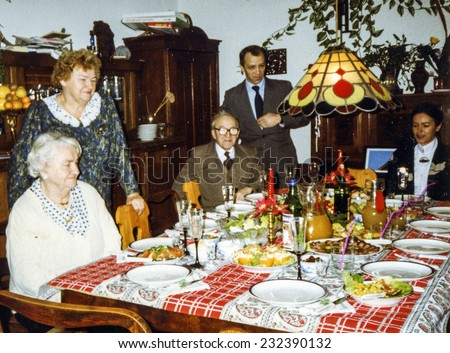 Vintage photo of elderly woman and her family during a Christmas dinner, eighties
