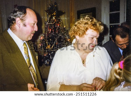 Vintage photo of elderly woman blessing her family and sharing Christmas wafer during Christmas Eve Vigil, eighties - stock photo