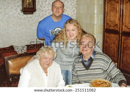 Vintage photo of elderly woman with her daughter in law and grandchildren, nineties - stock photo