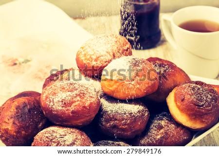 Vintage photo of falling powder sugar on donuts. studio shot - stock photo