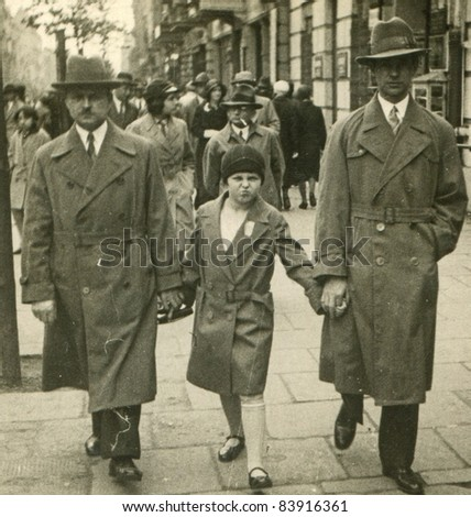 Vintage photo of family walking on the street (thirties) - stock photo