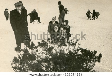 Vintage photo of father and children enjoying winter (fifties) - stock photo