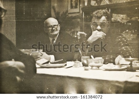Vintage photo of father and son during family dinner (sixties) - stock photo