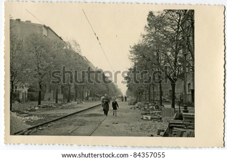 Vintage photo of father and son walking on the street during road works (thirties) - stock photo