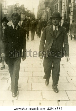 Vintage photo of father and son walking on the street (thirties) - stock photo