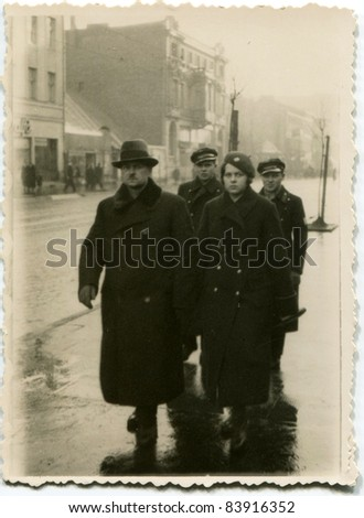 Vintage photo of  father, sons and daughter walking on the street (thirties) - stock photo