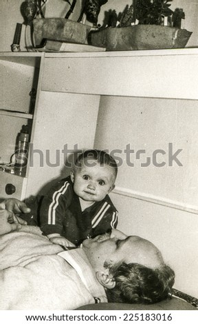 Vintage photo of father with baby daughter, early eighties - stock photo