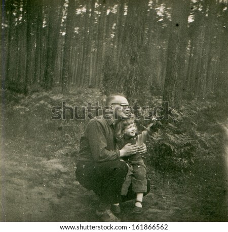 Vintage photo of father with little daughter outdoor, fifties - stock photo