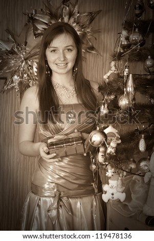 Vintage photo of girl near decoration spruce with christmas gift - stock photo