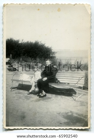 Vintage photo of grandmother with her granddaughter on bench