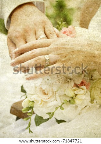 Vintage photo of hands and rings on wedding bouquet