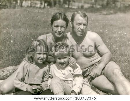 Vintage photo of happy parents with children (eighties) - stock photo