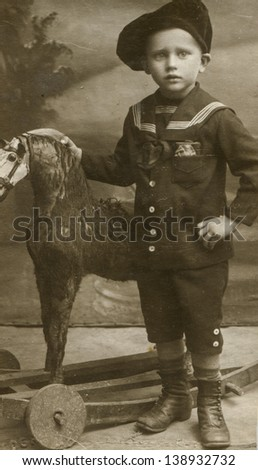 Vintage photo of little boy with a horse toy (circa 1902) - stock photo