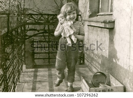 Vintage photo of little girl with a doll (fifties) - stock photo