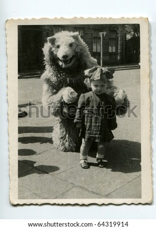 Vintage photo of little girl with fake bear - stock photo
