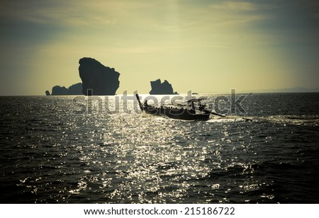 Vintage photo of longtail boat travelling on sea at sunset
