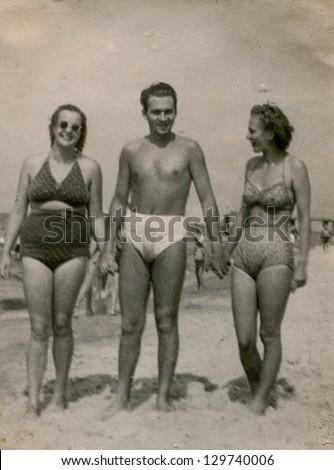 Vintage photo of man and two women in bathing suits on beach (thirties) - stock photo