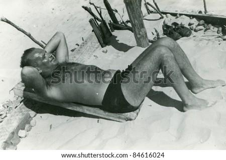Vintage photo of man on beach  (fifties) - stock photo