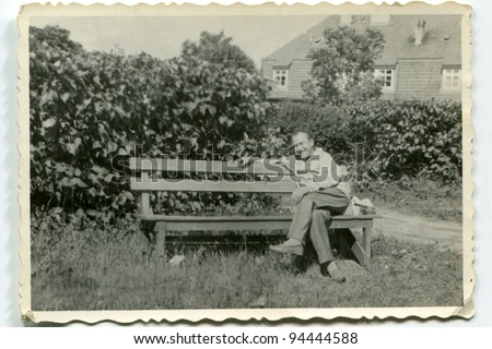 Vintage photo of man on bench (fifties) - stock photo