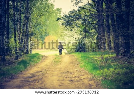 Vintage photo of man walking by forest path. Photo with vintage mood effect - stock photo