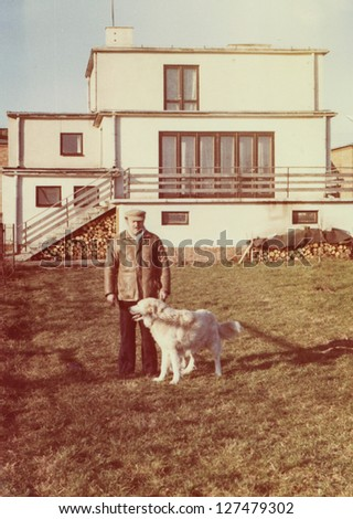 Vintage photo of man with a Shepherd dog, early eighties