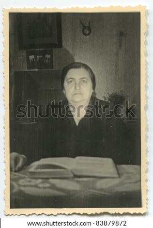 Vintage photo of mature woman reading (fifties) - stock photo
