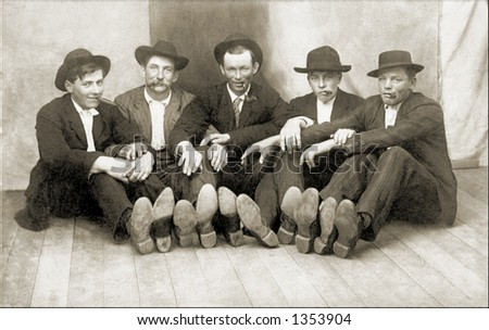 Vintage photo of Men Sitting On Floor With Feet To Camera - stock photo