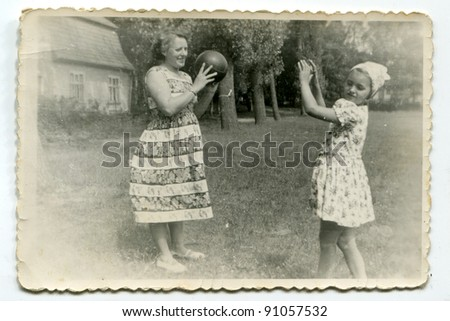 Vintage photo of mother and daughter playing ball (fifties) - stock photo